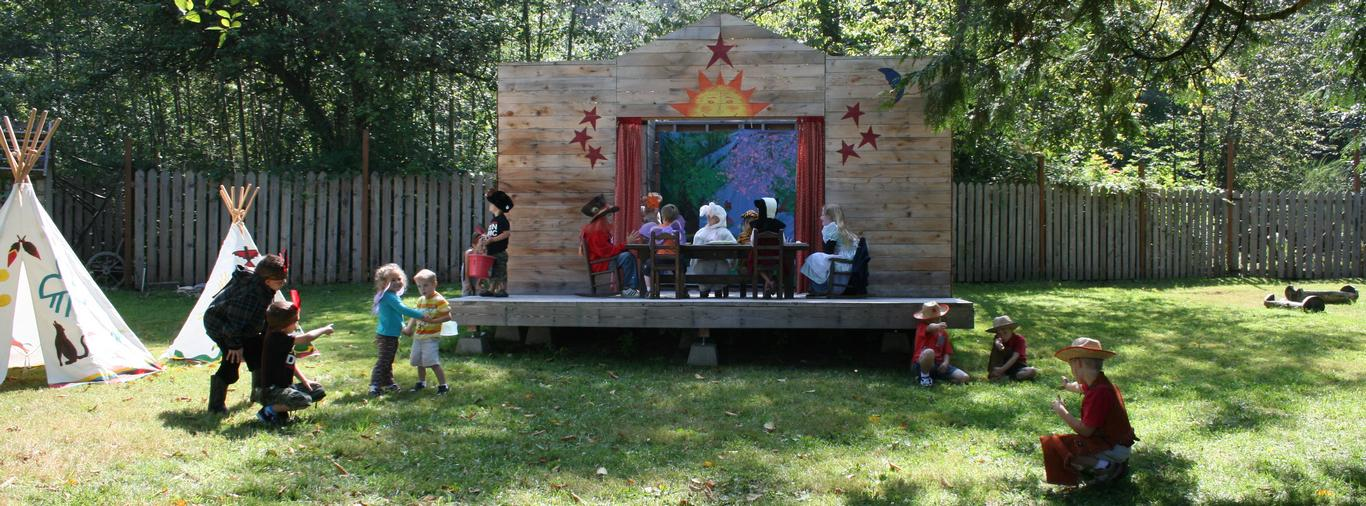 Children create and perform a play on their own outdoor stage