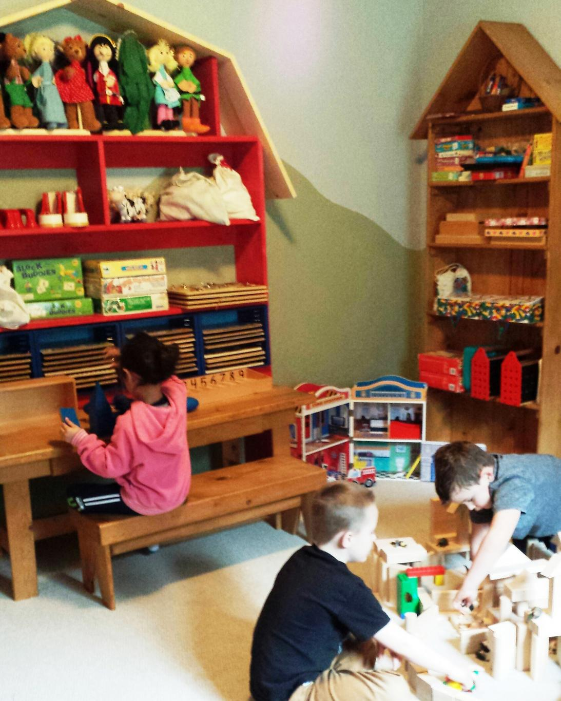 Indoor play room has shelves filled with baskets of toys and books