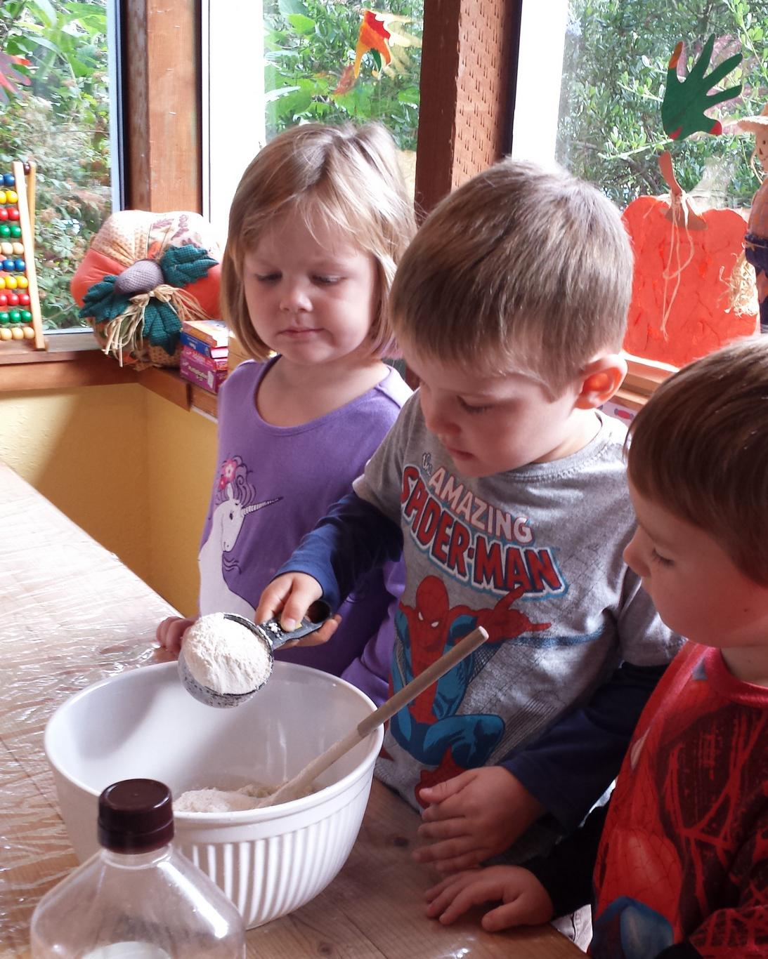 Children learn to make bread at Village Learning