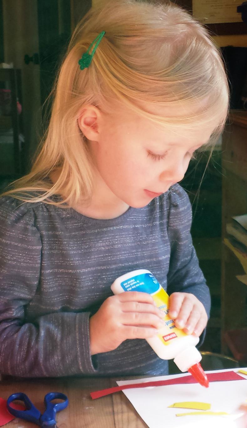 Girl gluing an art project by herself