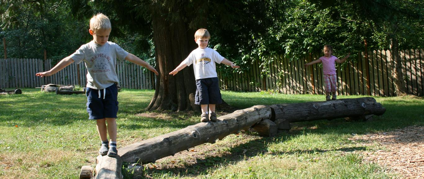Children learn new skills while walking the outdoor balance beam