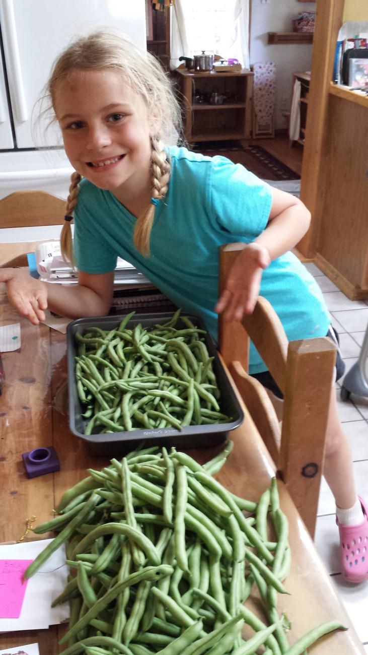 Girl shows off green bean harvest from the garden