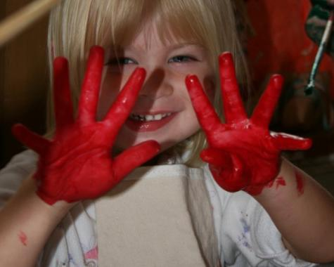 Girl with red paint hands loves her art