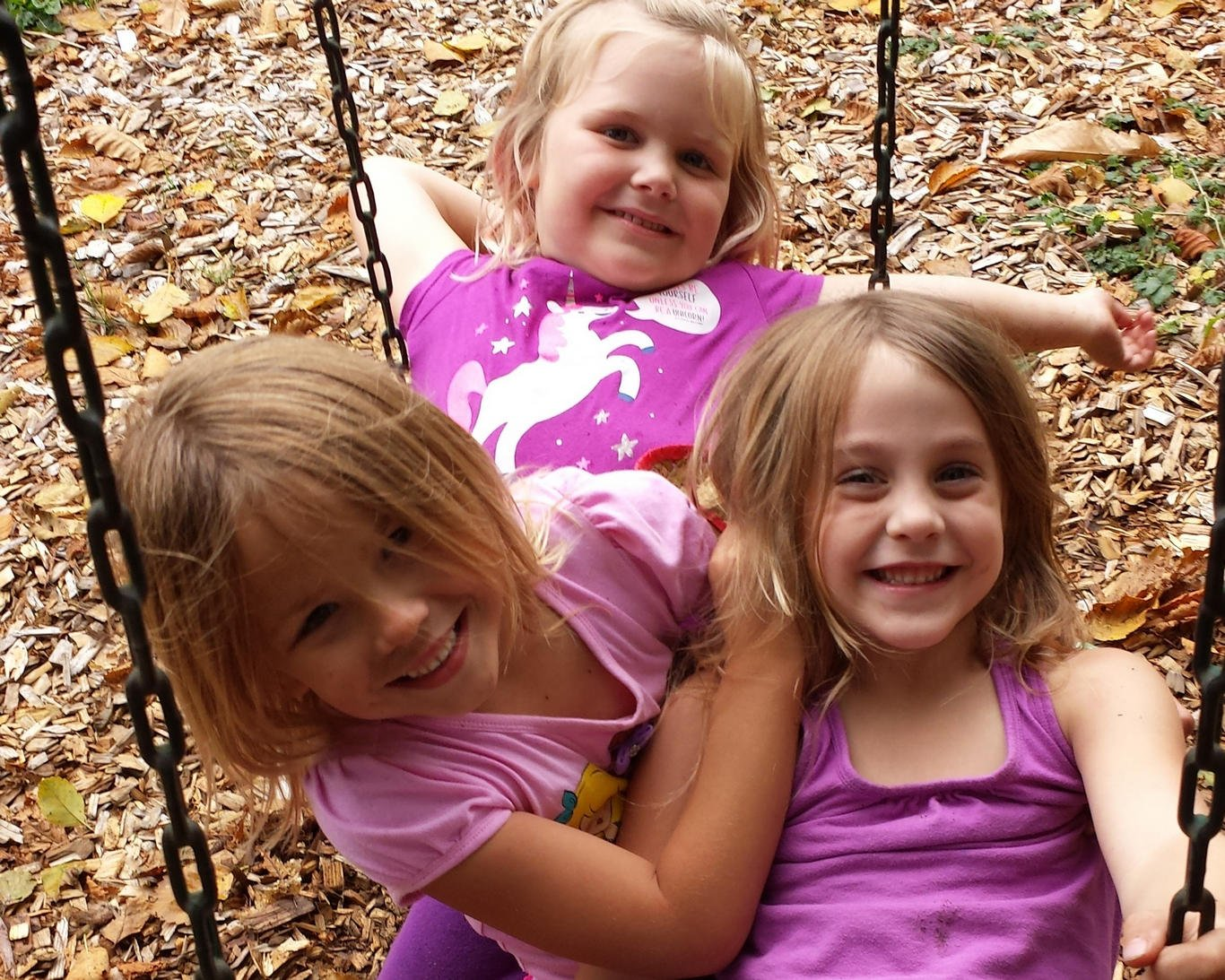 Preschool girls share a swing and a few laughs