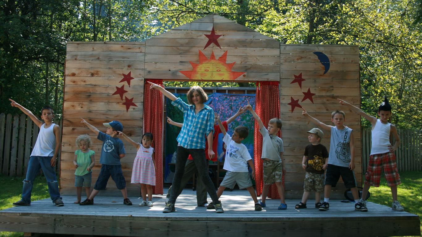 Children make costumes and perform a play on their outdoor stage