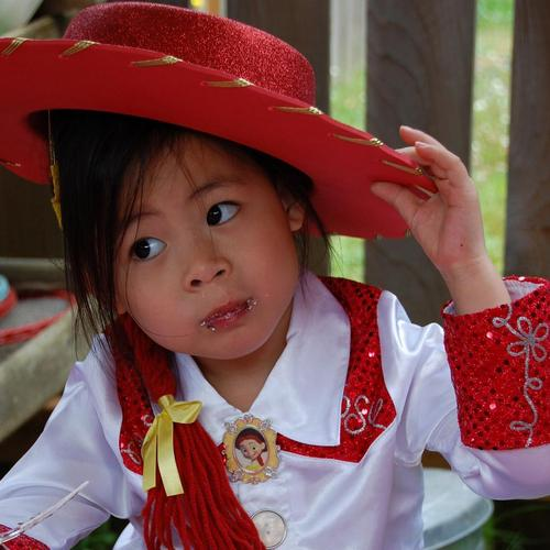 Girl tilts head while wearing cowboy hat