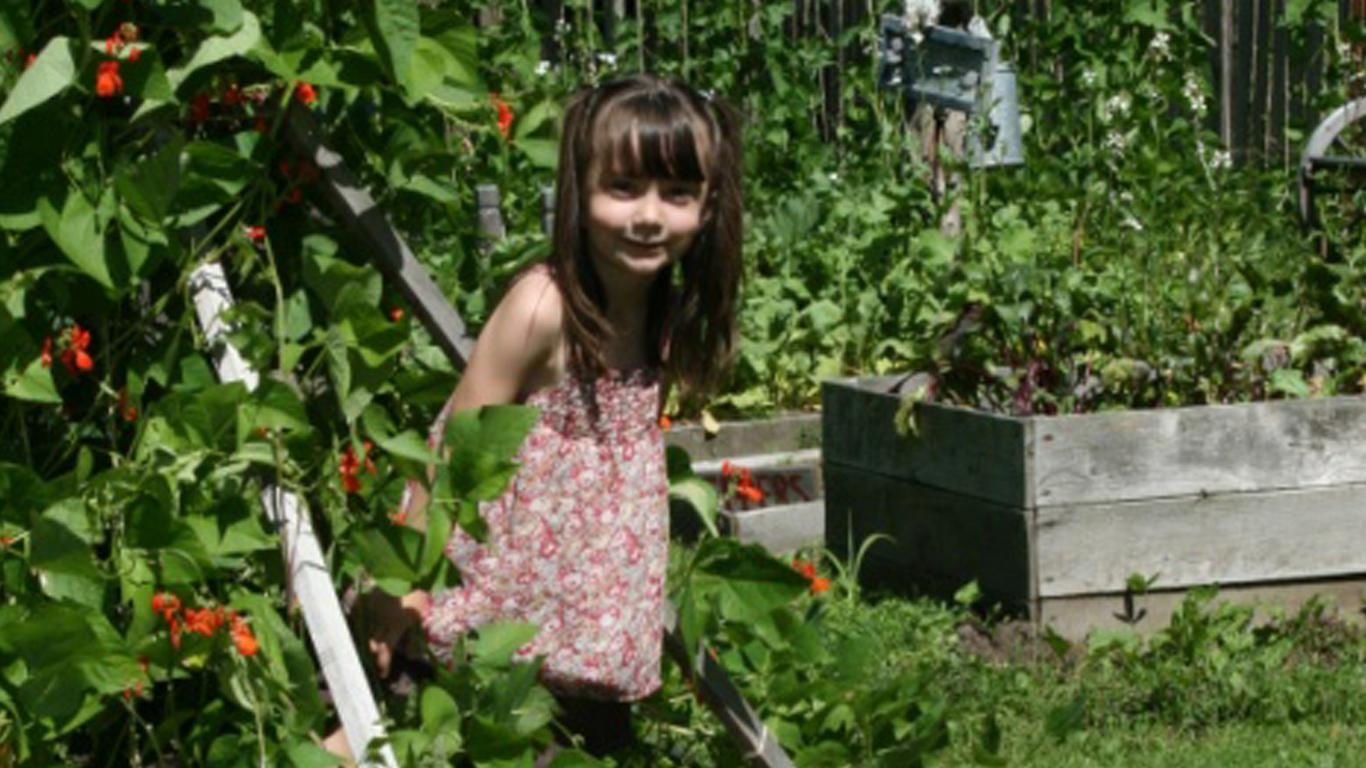 Girl explores garden at First Love Farm, part of Village Learning Child Care