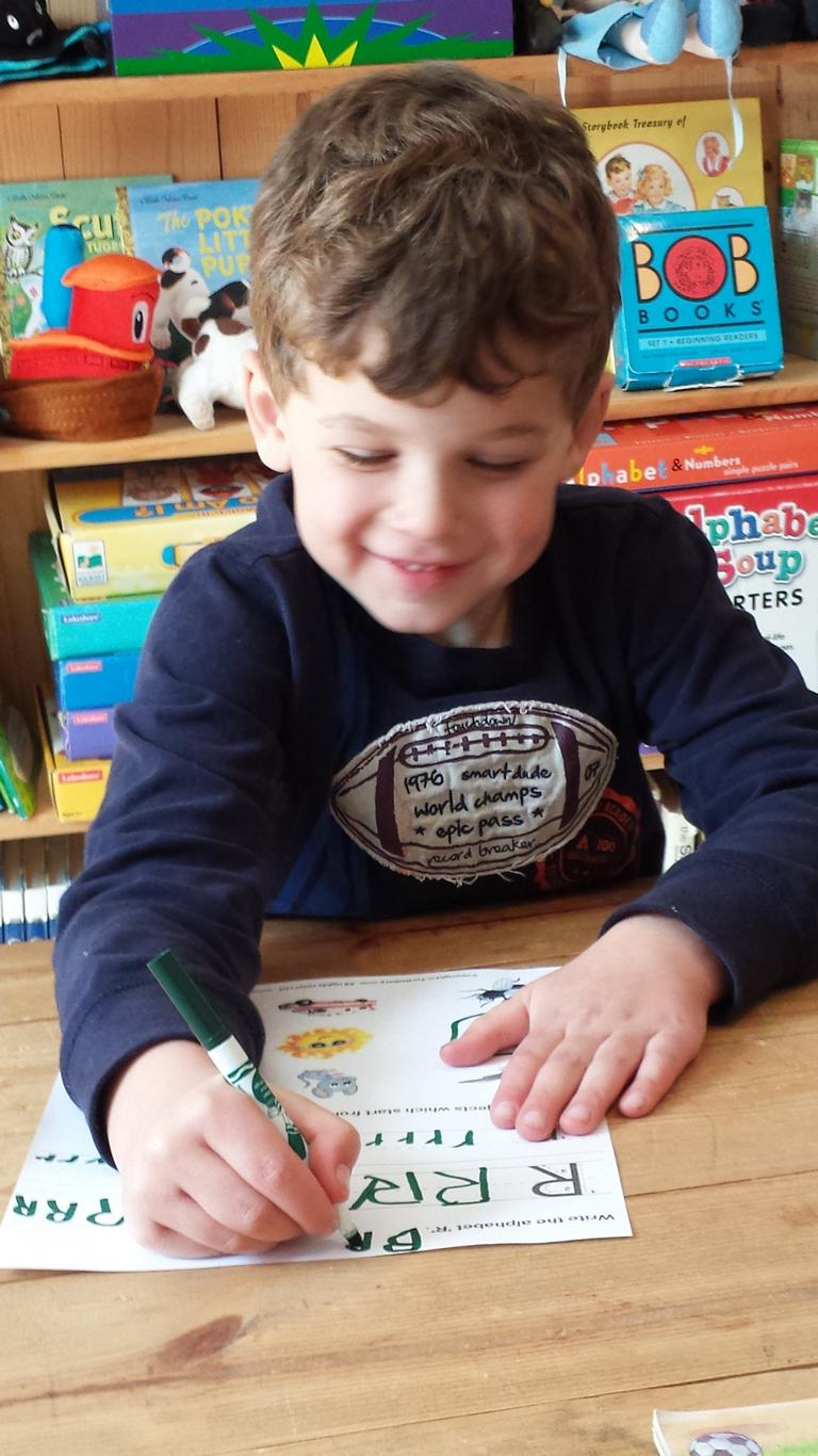 Preschool boy learns to draw (or build) letters as a form of art