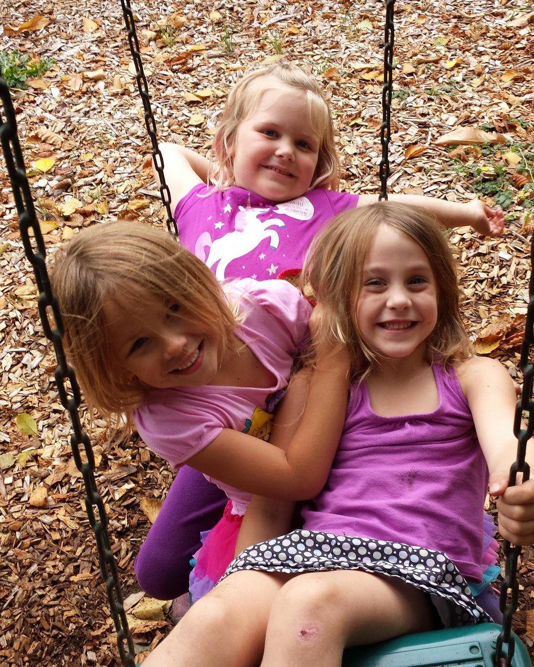 Girls share a swing in the preschool program at Village Learning